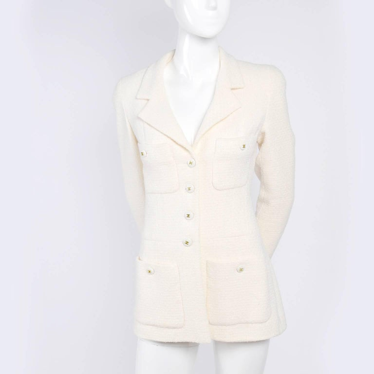 This is an absolutely gorgeous vintage Chanel blazer or jacket with CC logo buttons and tone on tone CC logo printed silk lining.  The jacket is in an ivory, almost cream wool blend fabric and it has 4 front pockets and a notched collar.  This