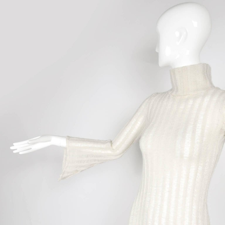 This is a gorgeous vintage knit dress in a ivory, almost cream, wool blend knit fabric.  The turtleneck dress has pretty bell sleeves and is sheer where the open weave of the fabric forms vertical stripes.  We estimate this to fit a modern day size
