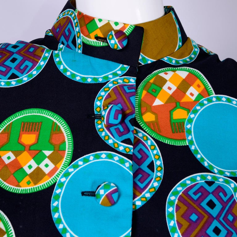 This cotton print vintage dress was made by Dynasty for I Magnin in the 1970's. We love the gorgeous print of abstract circles in shades of turquoise, orange, green, purple, copper and white. The dress has fabric covered buttons on the bodice and
