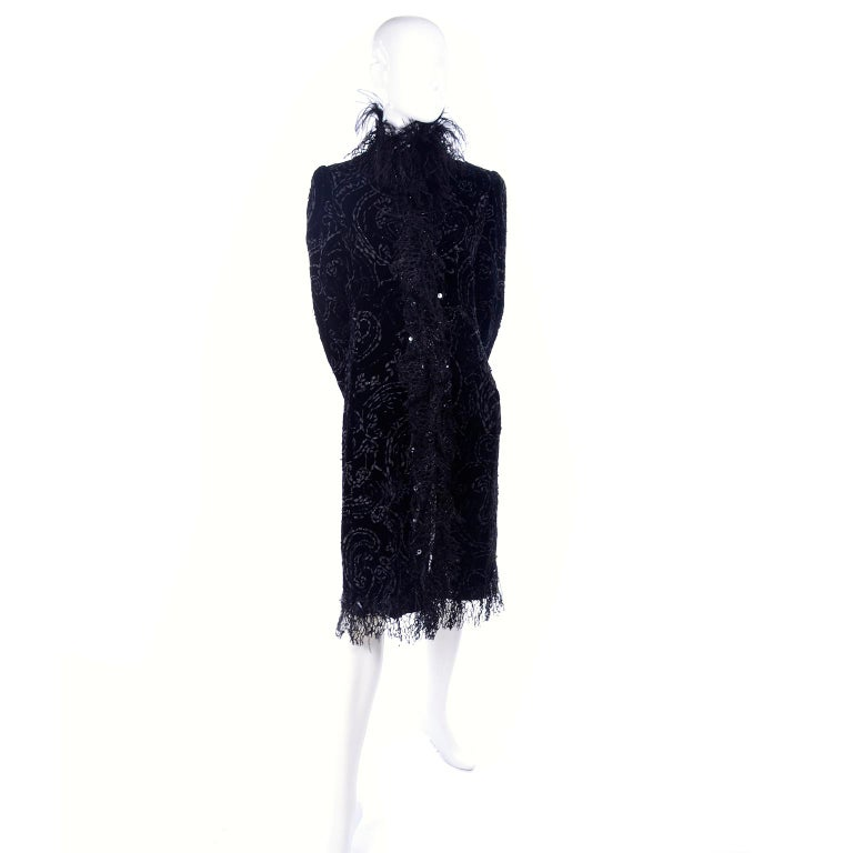 This is an incredible Oscar de la renta black velvet evening coat with woven ribbons, lurex lace, sequins, and ostrich feathers. The coat is simply stunning in person and would be perfect worn over a simple cocktail dress as it would add just the