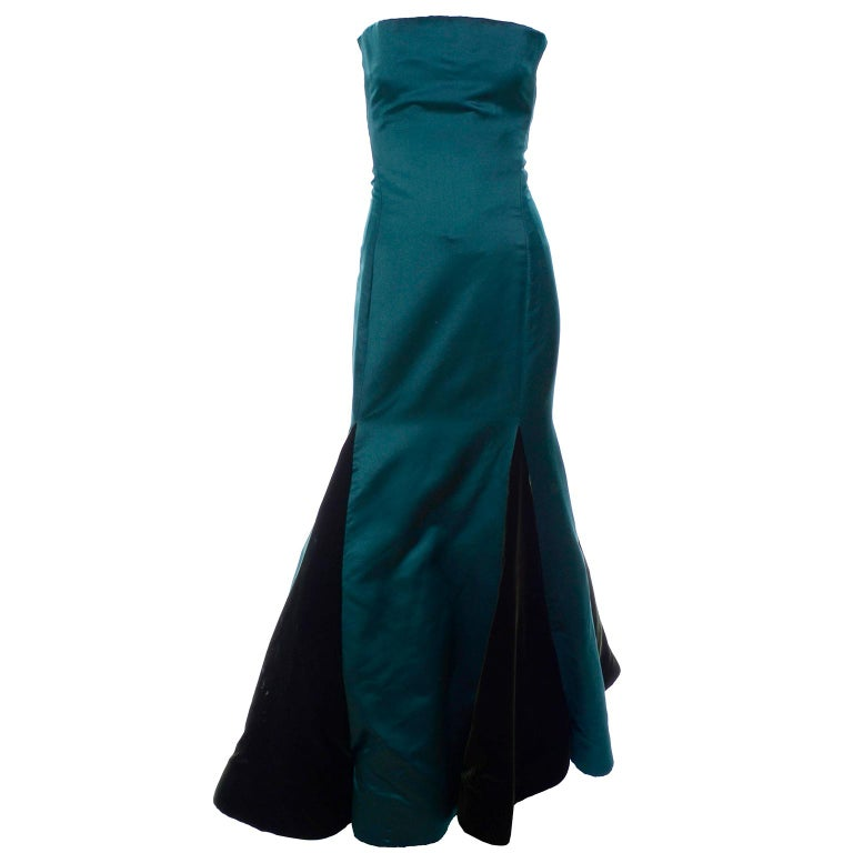 This incredible vintage green dress was designed by the incomparable Arnold Scaasi.  This stunning evening gown is strapless with a gorgeous uniquely cut bodice and a trumpet skirt that has alternating rows of velvet and satin. The dress is fully