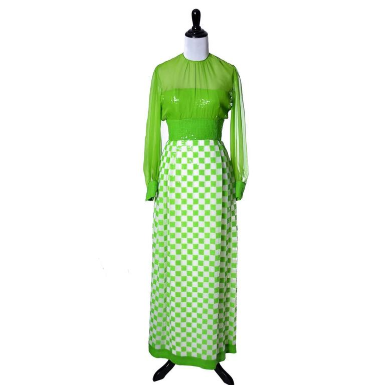 This incredible dead stock Adele Simpson late 1960s dress is a beauty, with green and white checks and sequins on 100% silk. The sleeves and over blouse on the bodice are silk chiffon, the bodice underneath is strapless and it is covered with green