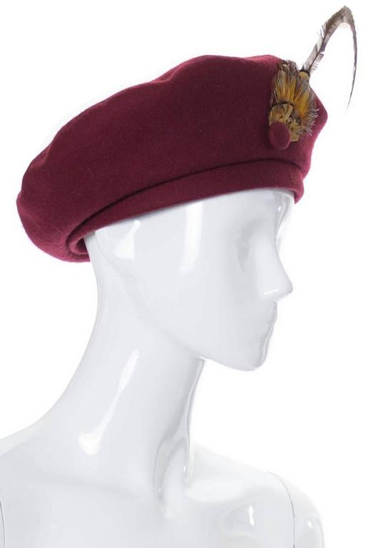 This beautiful Adolfo II vintage hat came from an estate of absolutely incredible mid century  designer vintage clothing and accessories. This wool beret is in a beautiful shade of burgundy and has a lovely feather and covered button that add just