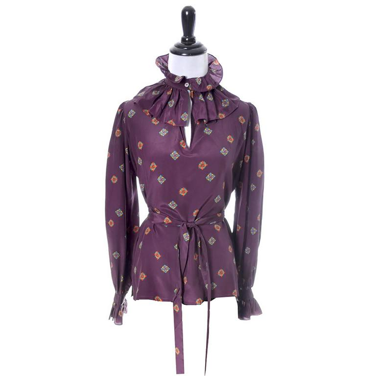 This pretty vintage Yves Saint Laurent Rive Gauche 1970's silk blouse has a ruffled collar and ruffled cuffs, a key hole opening, and a sash / tie that can be worn as a bow around the neck or as a waist belt.  This YSL blouse is in a rich plum silk