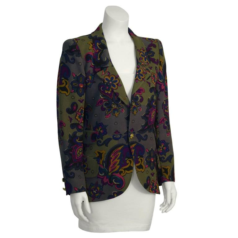 Funky Ungaro khaki floral blazer from the 1980's featuring notched lapels, a single button closure and two patch pockets at the hip. Gold plate button with ornamentation. Paisley print has notes of magenta, purple, teal and mustard. Amazing way to