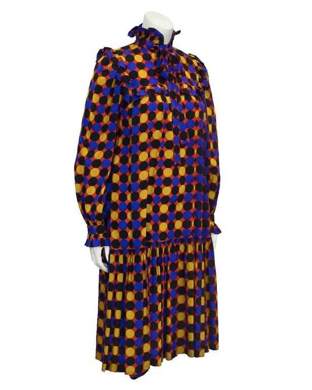1970's YSL full cut dress with black, royal blue and yellow polka dot pattern on red background. Full swing fit with drop waist and gathered hemline. Ruffled trim on the cuffs. Tie at neck and gathered yoke with inset ruffle detail extends to the