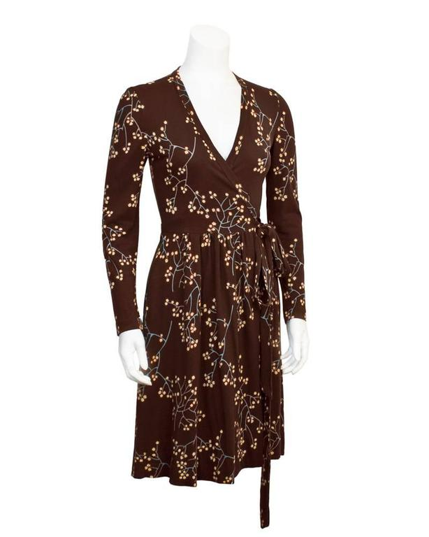 Iconic 1970's wrap dress by Diane von Furstenberg in a rich brown tone with delicate floral branches printed all over. The blue branches are adorned with red and yellow blossoming flowers, perfect for any season. The V neck style wrap does up on the