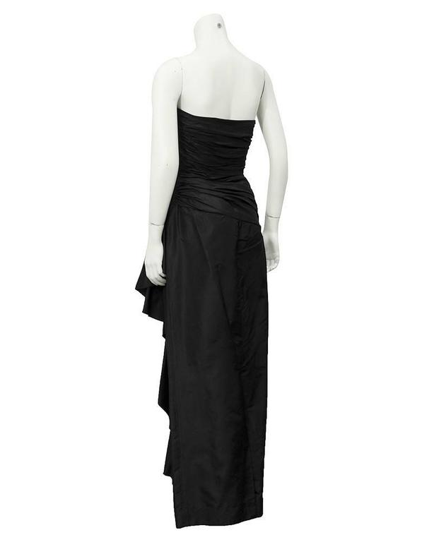 A fabulous 1980's Vicky Tiel black strapless gown. 100% silk and purchased at Bergdorf Goodman. The bodice is ruched and crosses over on the front. The ruching gets wider across the hips creating a draped effect over the lower stomach. The