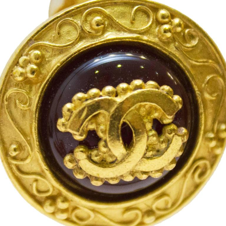 Chanel collection 1996 autumn gold plated and wine colored glass clip on earring. Lovely articulated borders with bead and swirl design. Center glass/resin is deep wine color with mounted CC logo gold plated decorative detail. In excellent