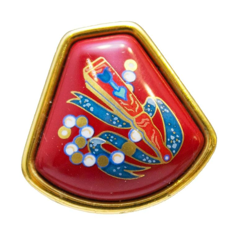 Elegant enamel clip on earrings from Hermes circa 1980. Signed on the back with the Hermes stamp. Modern fan shape with vibrant red enamel background featuring blue, gold and white Asian inspired imagery. In excellent condition. Medium size.  1in