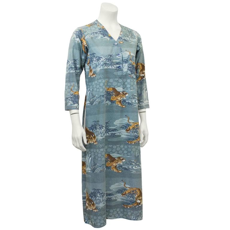 1970's Kenzo JAP blue cotton tunic featuring a Japanese jungle print of waterfalls and the iconic Kenzo tiger. Slits up both legs, 3/4 length sleeves, small pocket on left side of bust when wearing and v-neck with 3 button closure. Very early Kenzo