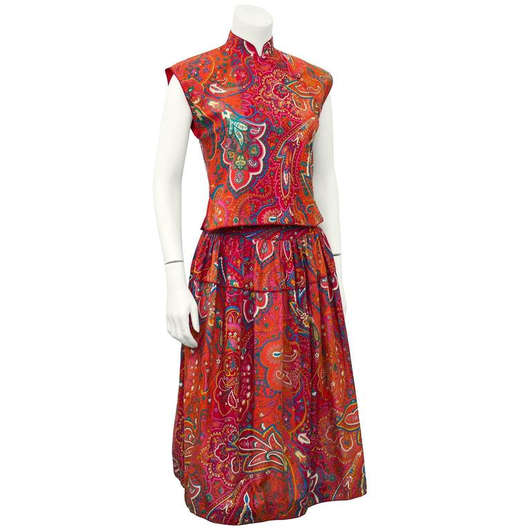 Playful cotton top and skirt set from Kenzo Paris, dating from the 1970's. Paisley print in warm, beautiful and rich orange and red tones, with contrasting blue and green. Top features cap sleeve, Mandarin collar and a-symmetric buttons. Gathered