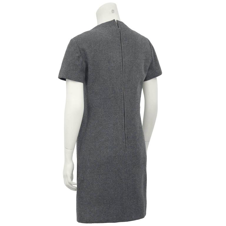 1960s Christian Dior New York grey wool flannel short sleeve dress. Grey wool covered single button detail, and zipper closure at back. Excellent vintage condition, timeless style with loose straight slightly belled shape, lining in tact. Fits like