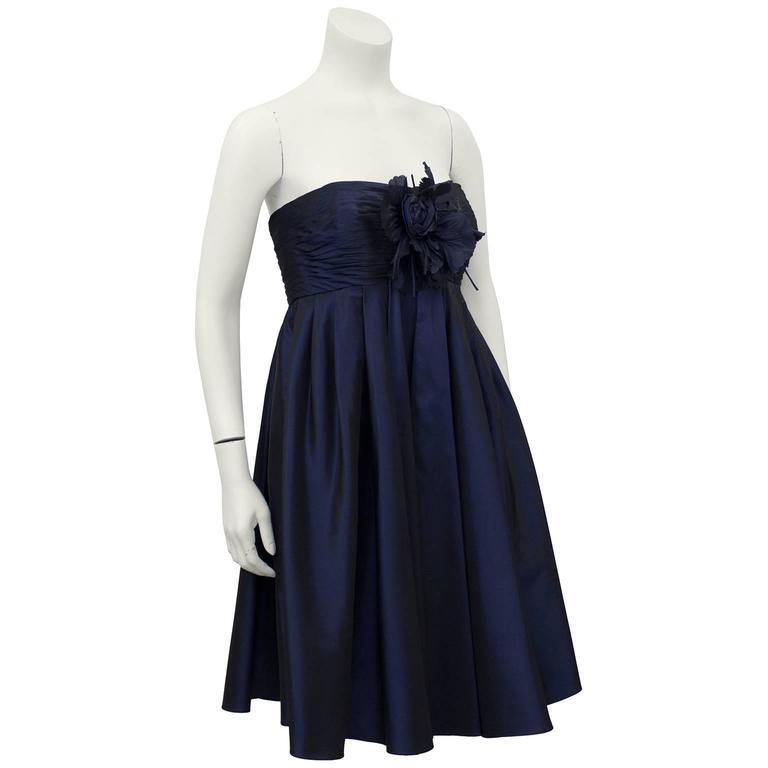 """1990's Bill Blass strapless navy blue silk taffeta empire waist cocktail dress featuring a large flower at bust. Boning through bodice. Excellent vintage condition, fits like a US 4.   Bust 32"""" Waist FULL Hips FULL Length 32"""""""