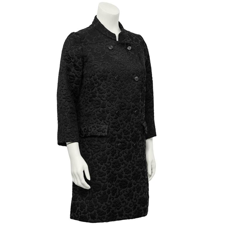 Beautiful 1970s black on black brocade coat by Tiktiner. Mandarin collar, 3/4 length sleeves and flap pockets. Belt detail at back. The perfect seasonal transition coat. Also easily dressed up as an evening coat. Excellent vintage condition, fits