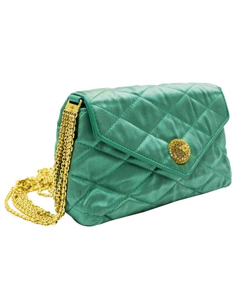 1980s Emerald green satin quilted Chanel evening bag. The soft silk bag is stitch quilted with a top flap and the CC logo stitched on the underside. The six strand gold chain strap is secured to the bag with matching emerald green leather tabs and
