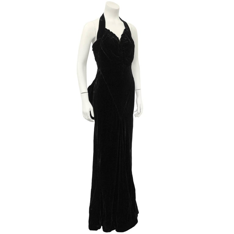 Incredible 1930's jet black velvet Chanel Haute Couture gown. Halter neckline with ruching throughout bust. Fitted through bust and skim the waist and hips, with a very slight mermaid skirt and very small train. Oversized bow at back, under button