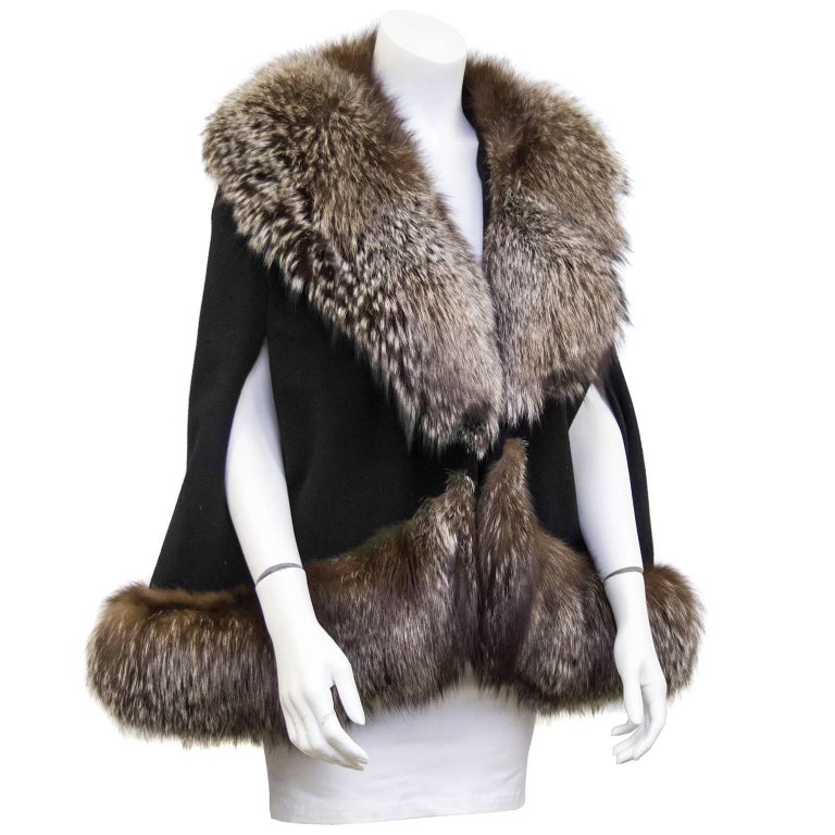 """Stunning 1970's short black wool cape with large brown/grey fox fur trim. Large fur hook closure. Perfect for a winter evening. Excellent vintage condition. Fits a US 2-8.  Shoulder 20"""" Bust 44"""" Waist 50"""" Hips 56"""" Length 30"""""""