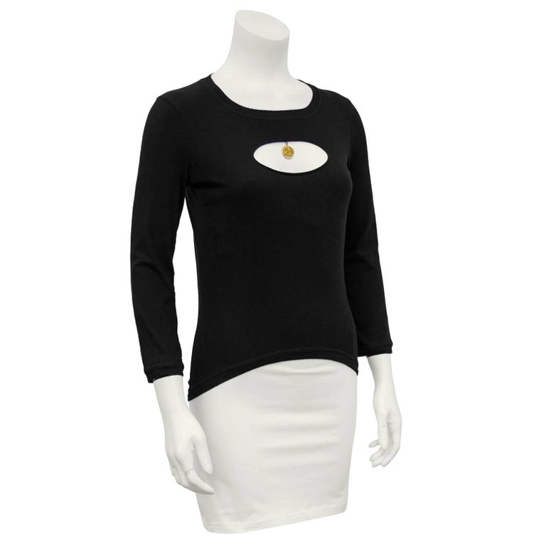 """1990s Chanel black stretch cotton long sleeve top. Cut out at bust to reveal a little cleavage with a gold glitter hanging coin. Hem is slightly curved at front and is longer in the back. Excellent vintage condition.   Sleeve 17"""" Shoulder"""