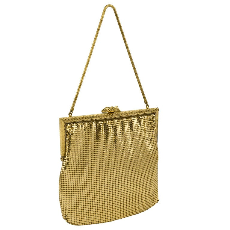 Classic and beautiful 1950s gold metal mesh evening bag. Details are amazing throughout, gold metal frame with ornate metal work and filigree snap clasp. Peach silk lining. Excellent vintage condition, slight wear to lining.   Length 7