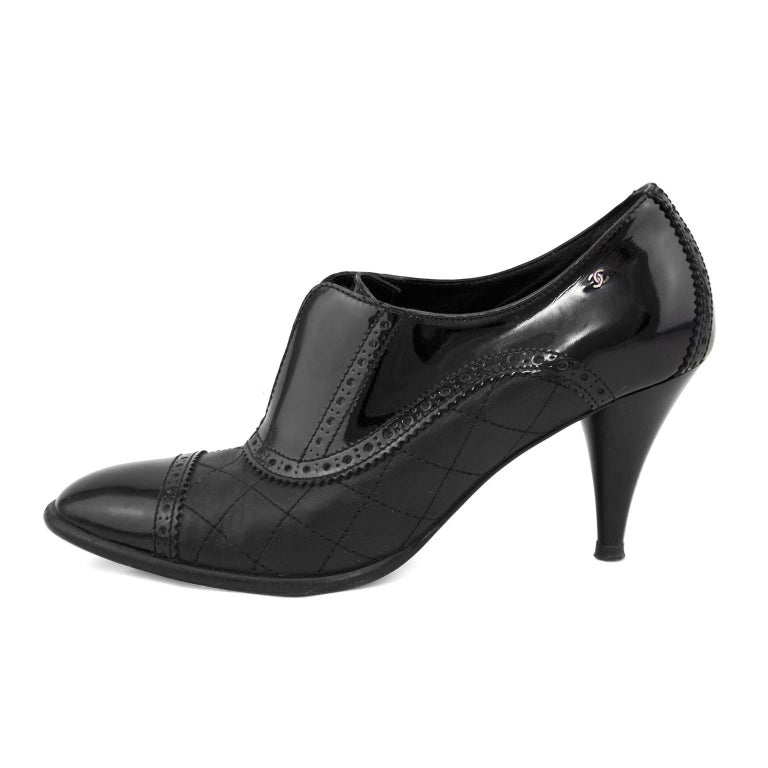 1990s Chanel black brogue pumps with quilted leather body and black patent leather accents. Broguing details throughout and tiny CC on the outer heel. In excellent condition with some signs of wear to the sole. Marked FR 39.  Fits like a US size 9.