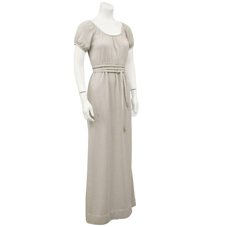 Bonnie Cashin leather trimmed heathered wool jersey gown in cream trimmed in tone on tone leather. The peasant style empire waist gown falls elegantly with some ruching just under the bust and ties with a leather skinny belt. Side slit pockets at