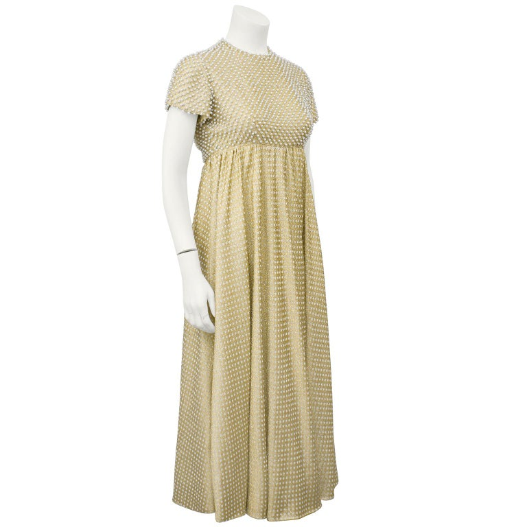 Stunning 1970's gold and white metallic knit maxi dress studded with pearls on the bodice. Capped sleeve, empire waist and flaired skirt combine well to highlight almost any figure. Currently ankle length. In fresh clean and ready to wear condition.
