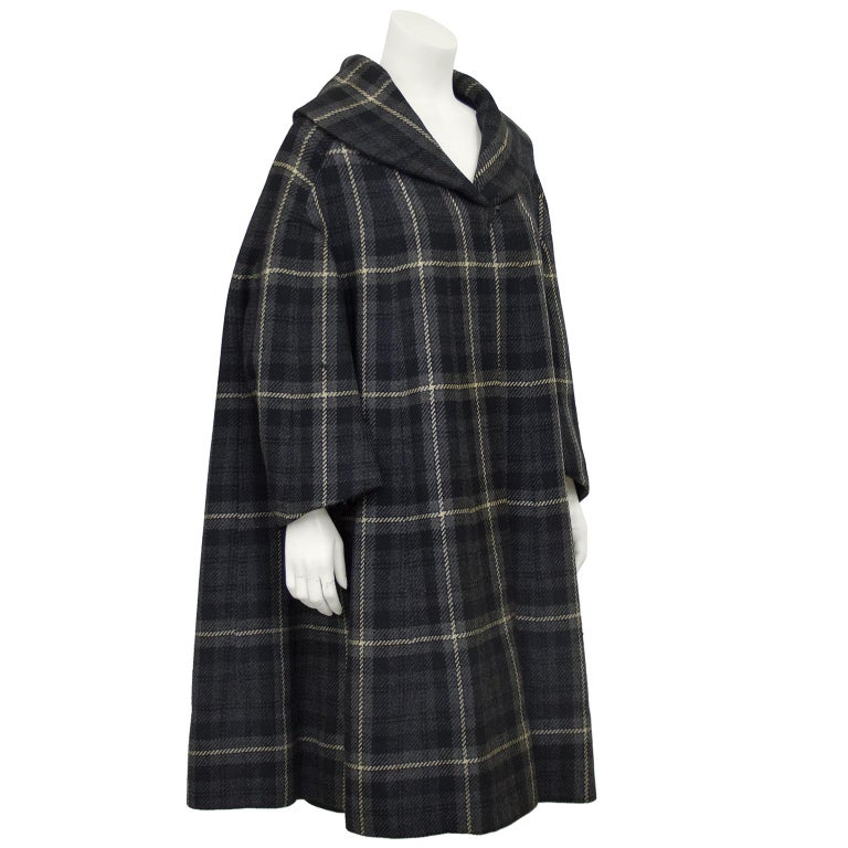 Plaid wool shawl coat by Balmain from the 1950s. Gray, black and cream plaid wool exterior and lined in black silk cotton. Full bracelet length sleeves and a single hook fastens at the bottom of the collar. Trapeze/swing style coat. In very good