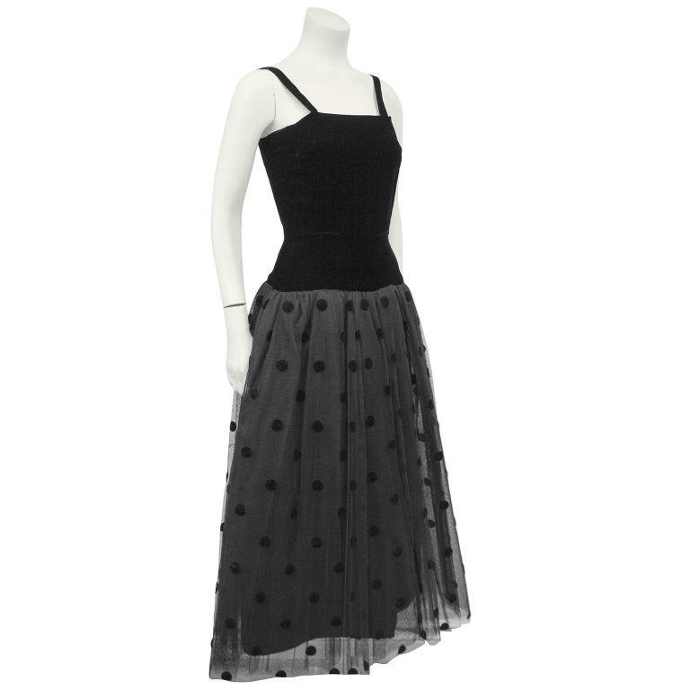 Anonymous 1980s black velvet drop waist dress with tulle skirt. The bodice has black shoulder straps and darts at the bust. Fitted through the body, the drop waist tulle skirt has black velvet polka dots throughout the top layer with 3 tulle layers