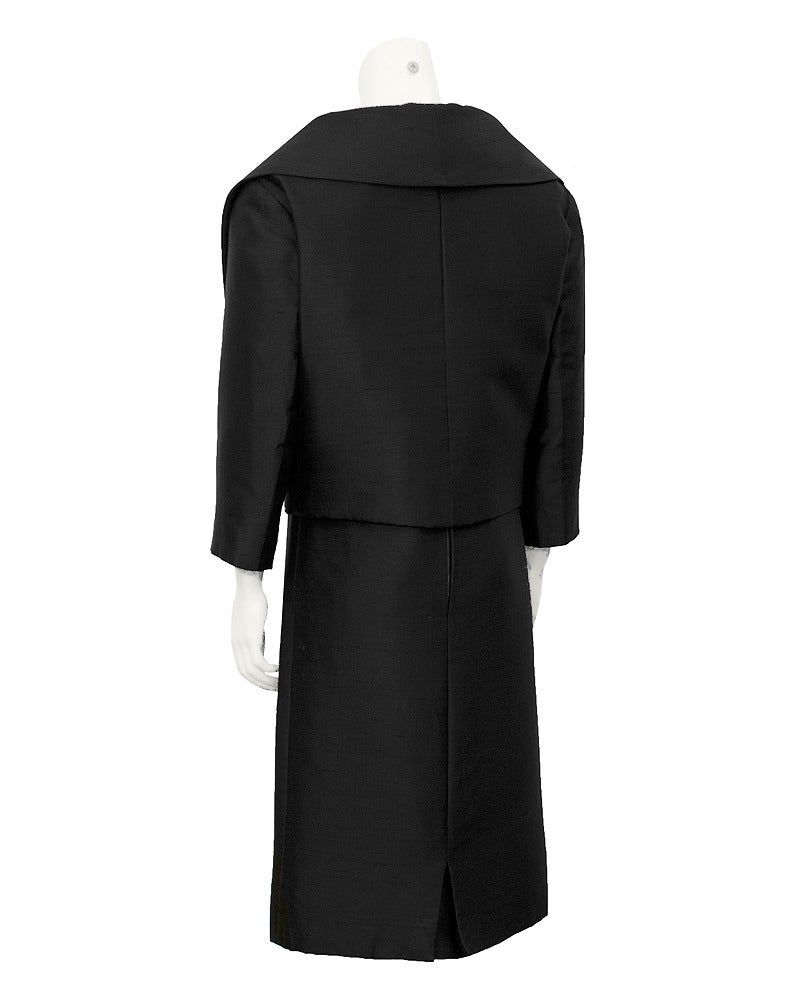 Black Christian Dior London raw silk jacket and dress ensemble pre 1957. The jacket has a wide shawl collar, bracelet length sleeves, straight front pockets and three silk covered front buttons. An adjustable front bow finishes off the jacket's