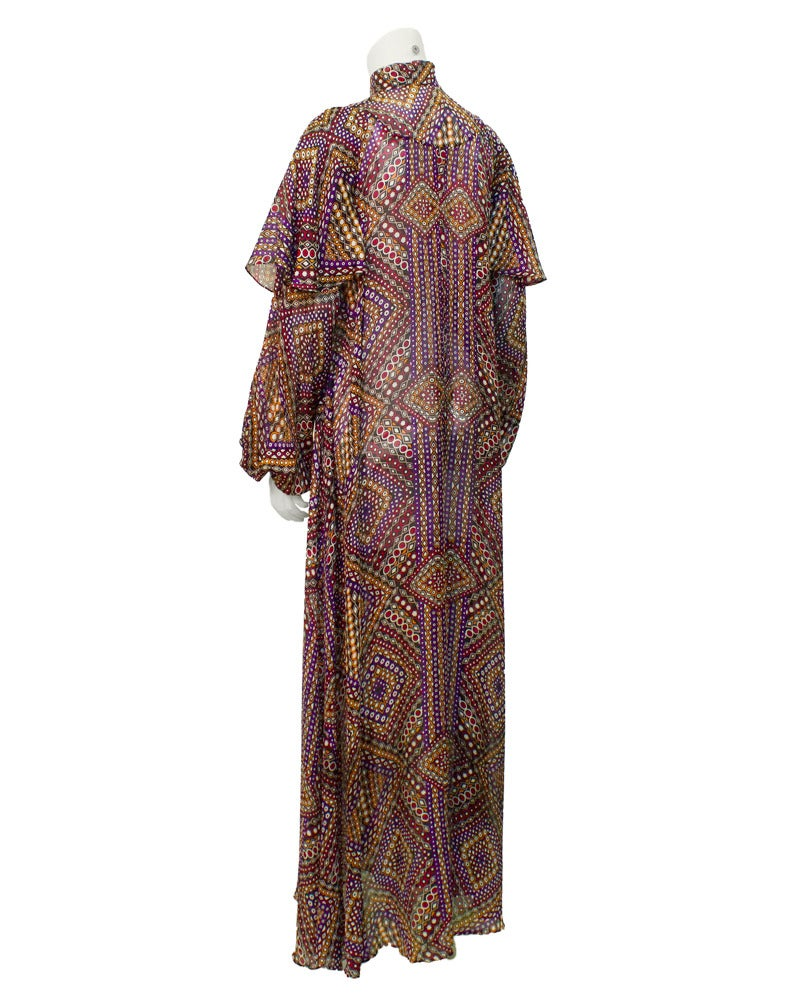 Enchanting late 1960's psychedelic chiffon geo print dress with a long, billowing and utterly romantic silhouette. Stand up collar with full balloon sleeves and gathered cuffs. Unique shawl like ruffle paneling along the armholes. Fastens all the