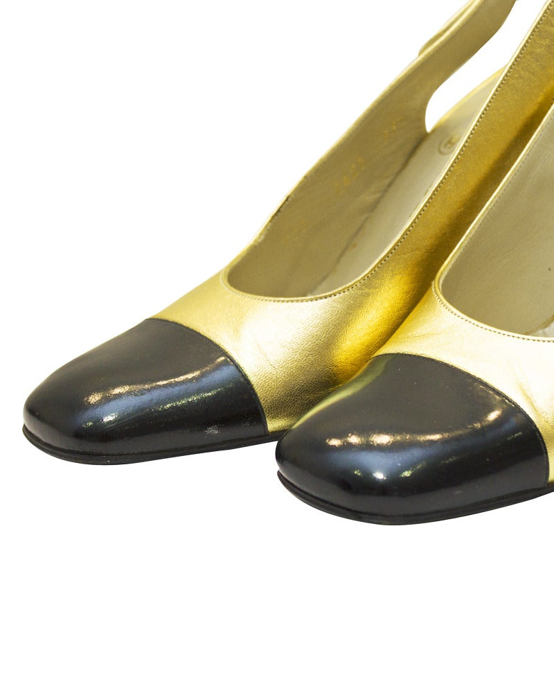 1990's gold leather Chanel sling back pumps with black patent cap toes and black heels. Slingback strap with gold-tone buckle closure with Chanel markings. Gold Chanel logo stamped on heels. In good vintage condition, rarely worn, minimal scuffing