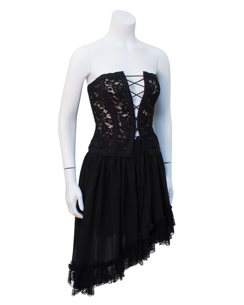 Late 1980's Saint Laurent Rive Gauche corset and skirt ensemble. Corset a has black lace overlay on top of a flesh colored lining. Corset lacing at the front is adjustable to your body. Skirt is a black silk chiffon and the bottom is trimmed with