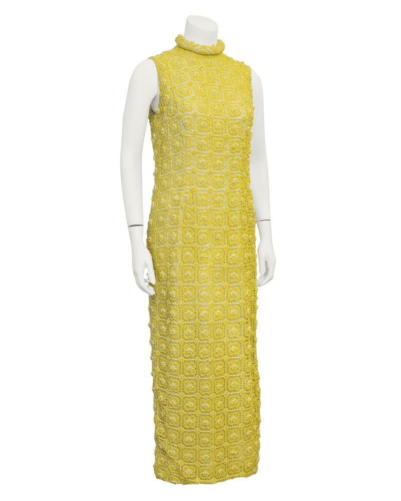 1960's gown and jacket ensemble by Marty Modell. Both gown and jacket have the most beautiful and delicate hand crochet fabric with white and yellow beading for detail over a cream colored lining. Gown is sleeveless with a high rolled collar. Jacket