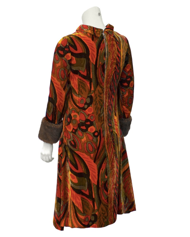Early 1960s cocktail dress by Teal Traina. Dress is made from stunning velvet full of rich fall tones of orange, brown and green in an abstract floral print. Mock turtleneck collar and cute mink cuffs. Inverted pleats at side seams add some flirt