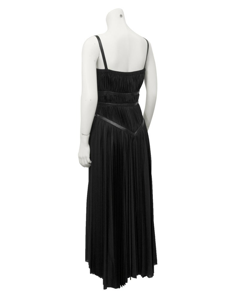 Size 44 black Prada ankle length polyester dress fashioned in a Grecian goddess gathered technique. The dress features black leather criss cross accents that wrap around the dress and fasten with a side zipper and two buckle style loop closures. The