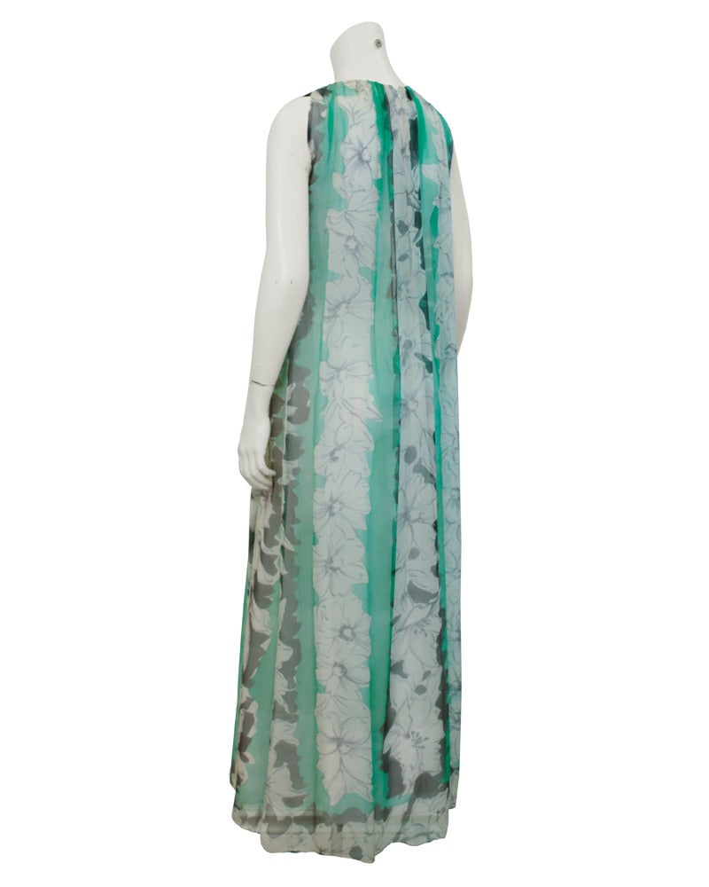 Gorgeous chiffon gown from the 1960s by Pauline Trigere. The gown can be worn two ways, with or without belt. The delicate chiffon falls in a loose gather from the neckline and is decorated with a grey floral pattern that runs vertically along soft