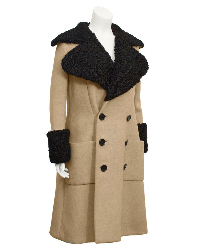 1970's beige wool Norell coat with exaggerated black Persian lamb fur cuffs and collar. Double breasted with large plastic black buttons and the quintessential Norell oversized rectangular pockets. Back has inverted pleat. Craftsmanship and weight