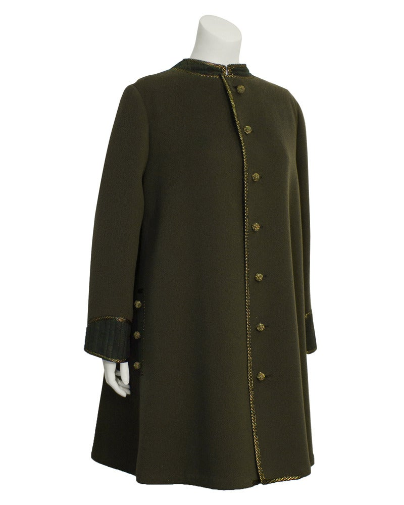 1960's Geoffrey Beene military inspired swing coat. Military khaki green wool with gold tambour stitching throughout the trim, pockets and woven buttons. Cuffs and upper back have green polka dot ribbed detail with gold fleck throughout. Simple