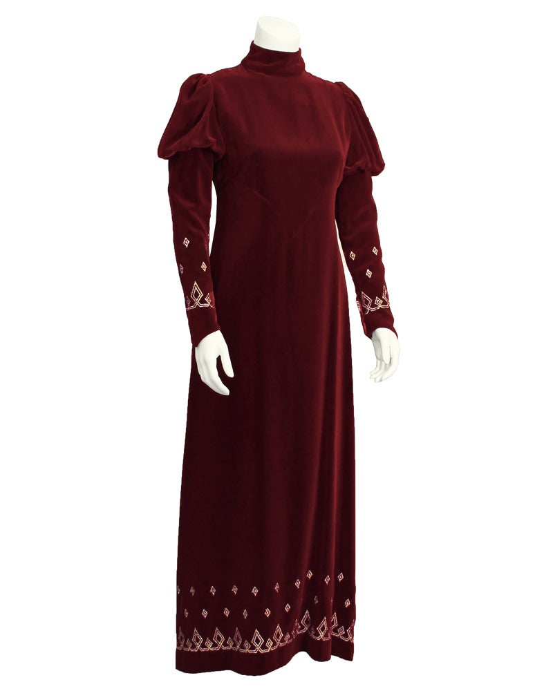 1970's burgundy velvet mock turtleneck, long sleeve gown. Mutton style sleeve at shoulder, tapers and elongates past the wrist forming a point. Very Directoire inspired 70's London Look piece. Bottom of sleeves and bottom of skirt are decorated with