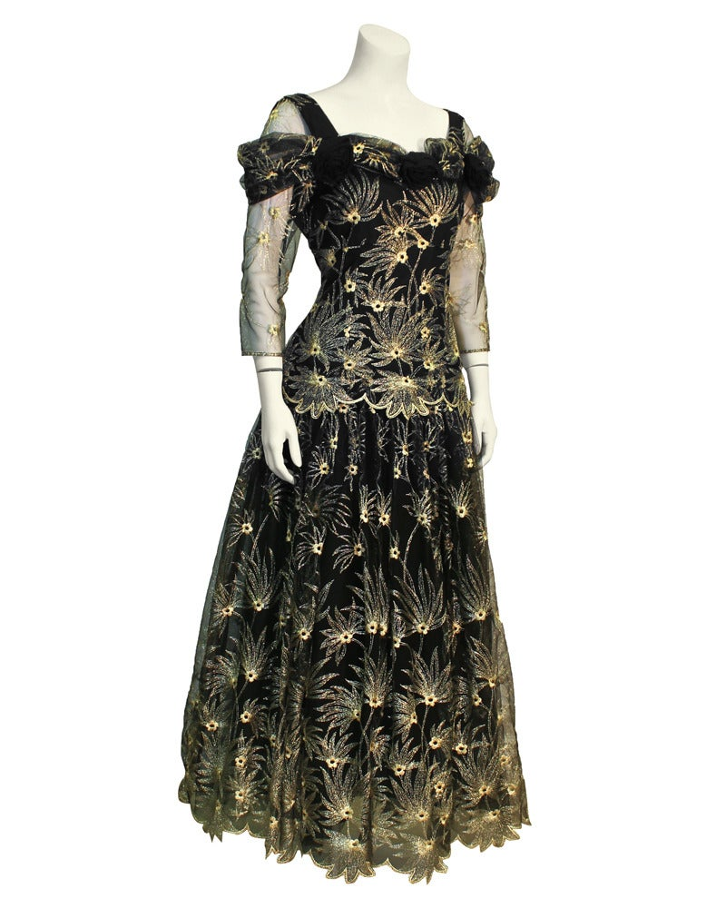 1980s Zandra Rhodes black gown covered in intricate metallic gold tambour stitched flowers and leaves. Gown features sheer long sleeves, black rosette appliques across at neckline and a drop waist with a full skirt. Incredible attention to detail.
