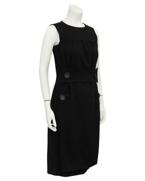 1960s Galanos black cocktail dress with a half front belt and four large leather covered buttons. Simply elegant, flawless design, timeless. Perfect day dress with boots or cocktail dress with diamonds and pumps. Excellent vintage condition.