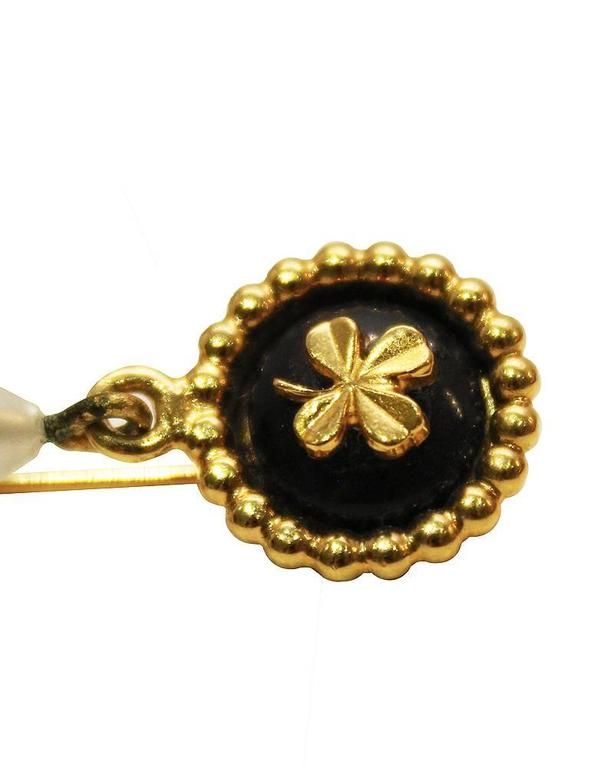 198'0s Chanel gold plate stick pin with a clover detail and a large teardrop shape faux pearl. Two of Chanel's classic logos. Excellent vintage condition.