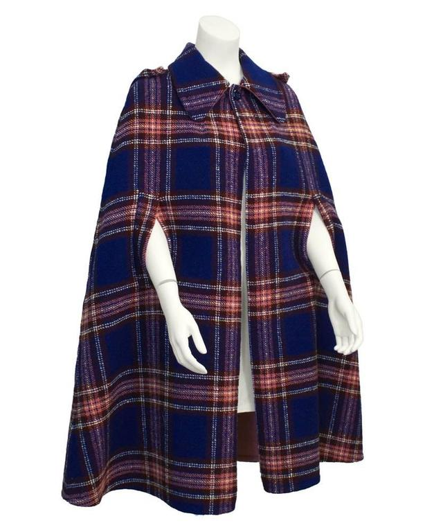 1960's blue, rose, white and brown plaid wool A-line cape. Single-button closure at neck, exaggerated collar with detachable hood. Rose wool lining. Excellent vintage condition. Generous fit, works well from US 6-10.