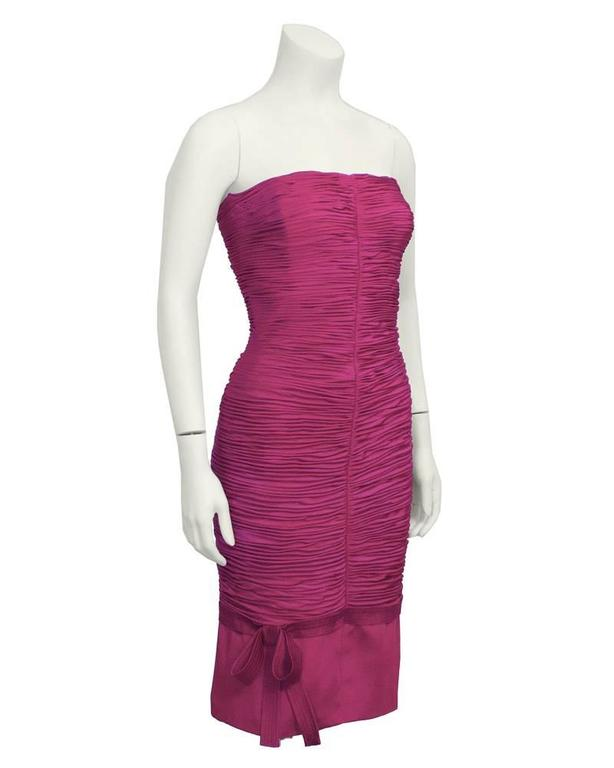 1990's Versace magenta form-fitting strapless Wiggle dress. Ruched silk with a centred vertical seaming creates a flattering body-conscious fit. Bow detail on bottom adds feminine touch. Back zipper with a hook closure. Fully lined with silk.