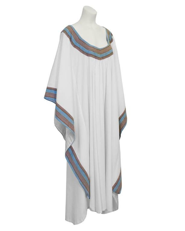 Fabulous white cotton kaftan from the 1970's. The neck and sleeves trimmed with with thick blue and brown woven tape. The perfect piece for a bohemian look. Very forgiving fit. Hard to find. Excellent vintage condition. Fits up to size 14 US.