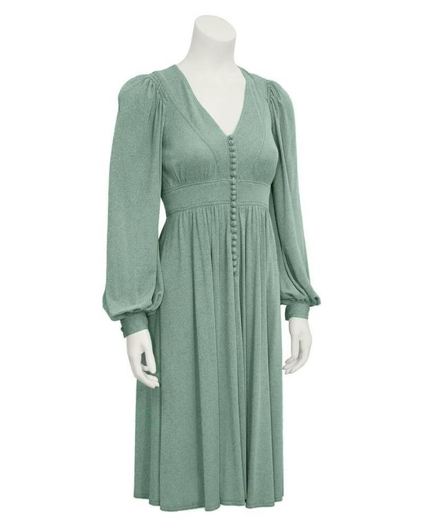 1970's British designer Jean Muir's heathered green knee-length day dress. Empire style waist line with soft draped pleats, pin tuck stitching, V-neck and loop buttons down center. Sleeves are gathered at shoulder and wrists, with buttons on each
