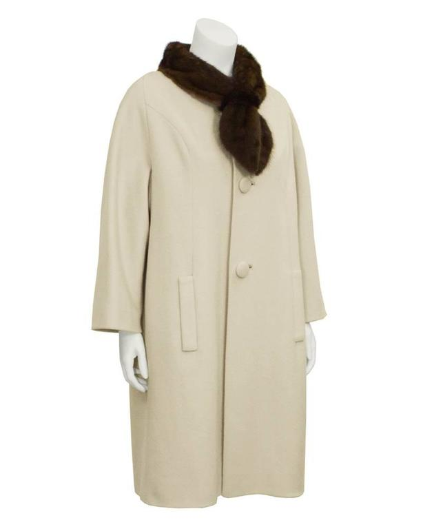 Lovely warm beige Lilli Ann wool coat dating from the 1950's. A-Line shaped with silk lining, an extended mink fur collar, slash pockets and large fabric buttons. Vertical seaming down front, and fixed pleats on back. Excellent vintage condition.