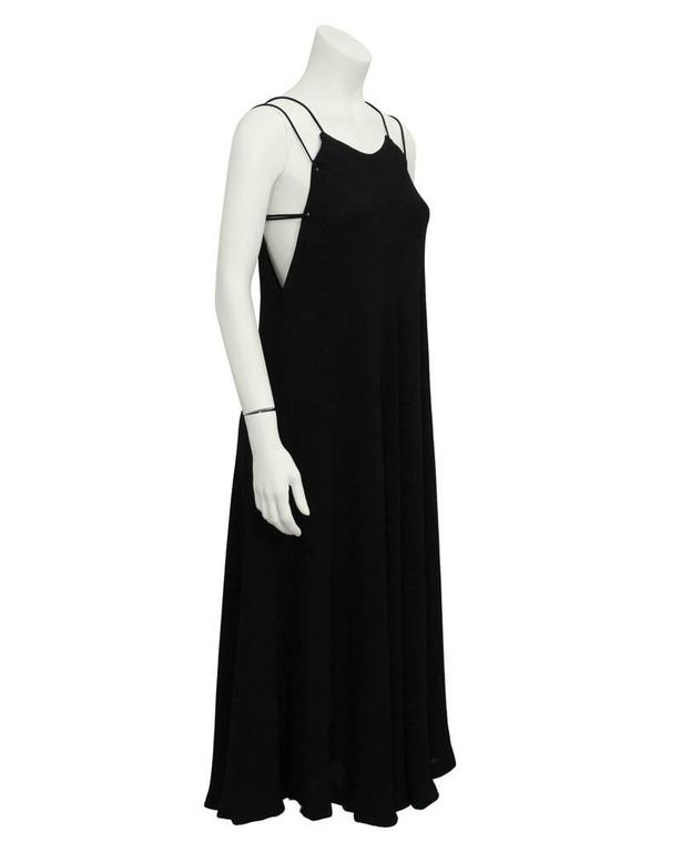 A simple and sleek black Halston gown that dates from the 1970's. High neck with two spaghetti laced straps that tie at the back. Loose-fitting swing cut. A go-to piece for any special event. Excellent vintage condition.