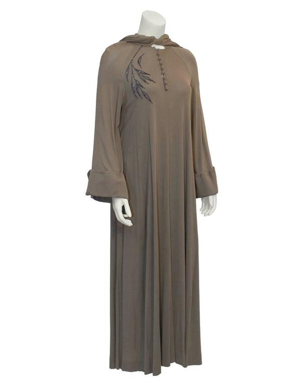 Stunning long-sleeve hooded Vicky Tiel gown from the 1980's. Mocha colored jersey material is draped, with beaded leaf design on the left shoulder. Small loop buttons down bodice. Excellent vintage condition. Generous fit from 4-8 US.